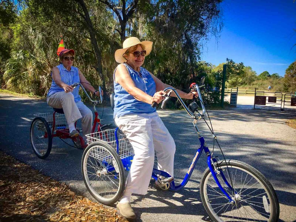 Two ladies on rental trikes from Venice Bikes and Trikes at Oscar Scherer Park on The Legacy Trail